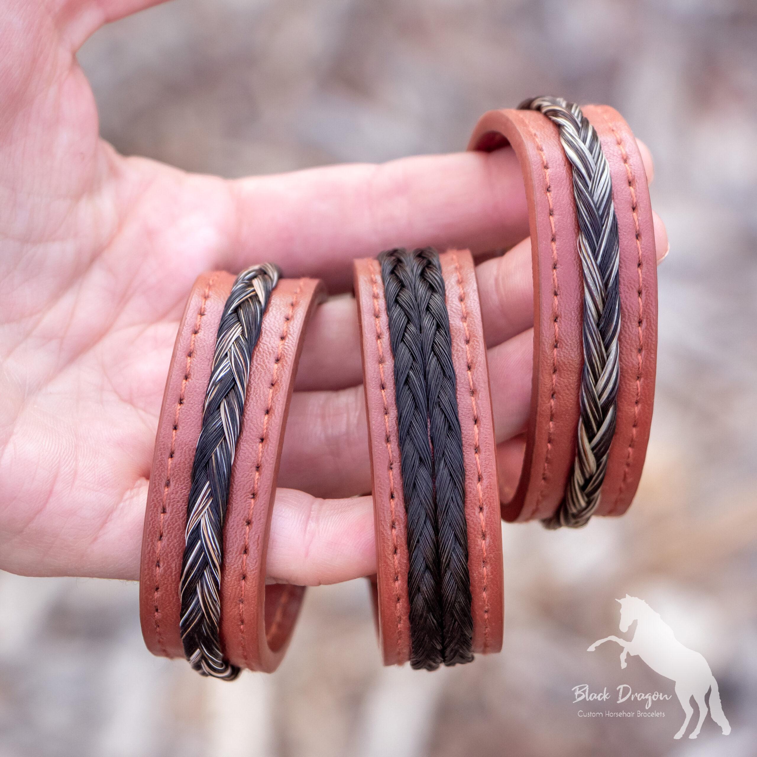 Hand holding three cognac leather horsehair bracelets